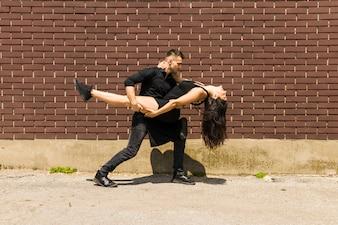 Сексуальная танцовщица танго танцует против стены