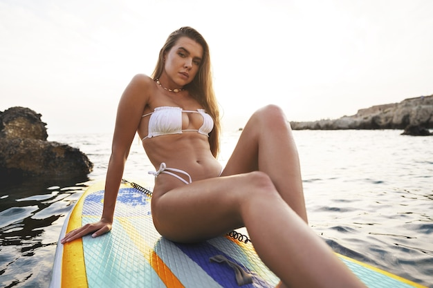 Sexy tanned girl in white bikini standing on sup board