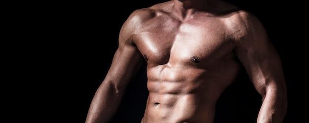 Сексуальный торс. красивый большой человек мышц позирует в студии. мускулистый сексуальный мужчина. красивый сексуальный сильный мужчина с мускулистым телом. торс с шестью кубиками и мышцами пресса. пресс и бицепсы. сильный брутальный парень.