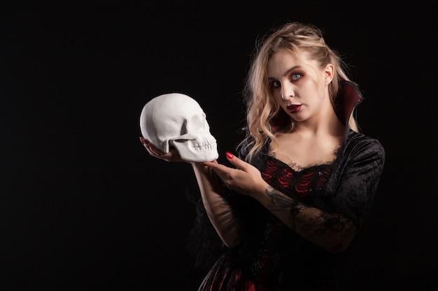 頭蓋骨を保持し、暗い背景で隔離のハロウィーンのカメラを見てセクシーな吸血鬼の女性。ハロウィーンの衣装。