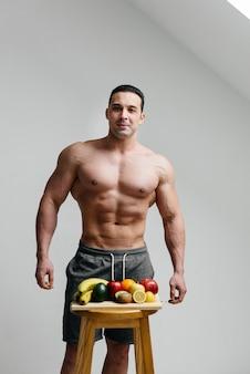 果物の横でポーズをとっている裸の胴体を持つセクシーなビーガンの男。ダイエット。健康的なダイエット。