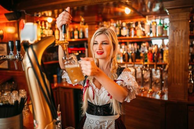 Сексуальная официантка наливает пиво в кружку у стойки в пабе.