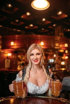 Sexy waitress in retro uniform holds mugs of beer