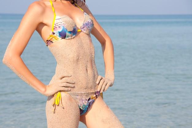 Сексуальная мокрая женщина в песке