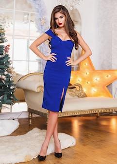スタジオの豪華なインテリアでポーズをとってエレガントな青いドレスでセクシーな白いモデル。ウェーブヘア