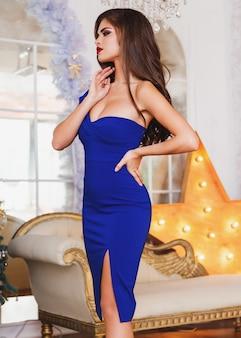 スタジオの豪華なインテリアでポーズをとってエレガントな青いドレスでセクシーな白いモデル