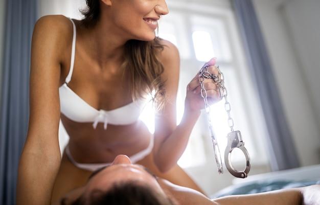 Сексуальная женщина и мужчина играют в игры с доминированием в постели