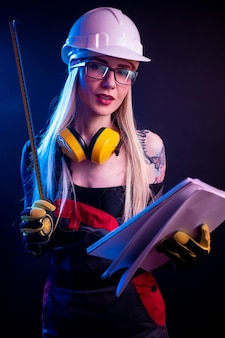 The sexy woman architect holding blueprints and wearing a helmet. in the neon light