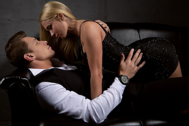 Sexy woman in a black dress kisses a beautiful man lying on the sofa