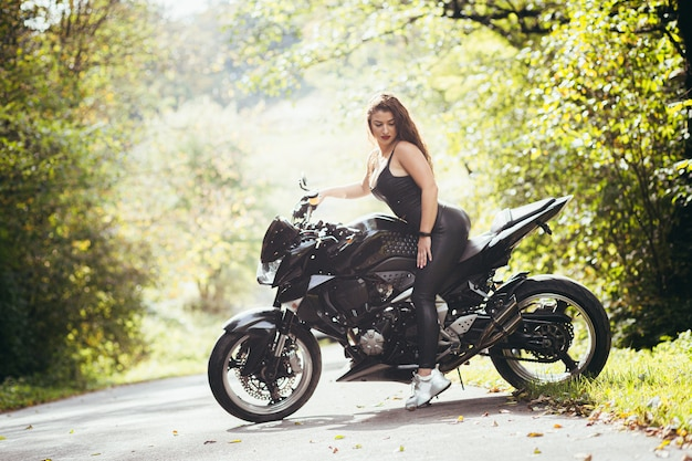 Sexy woman in black leather pants sitting on a black sports motorcycle