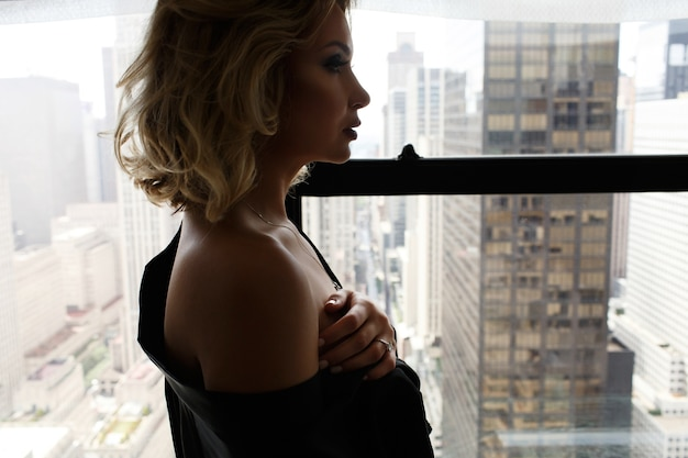Sexy woman in black silk robe stands with naked shoulders before a window in new york
