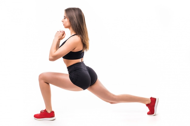 Sexy woman in black sportswear does exercises for strong figure body