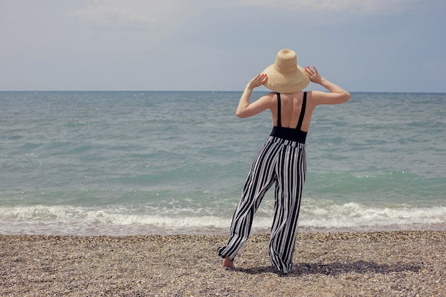Sexy woman in a black swimsuit, striped pants and sunglasses walk on the beach by the sea in summer