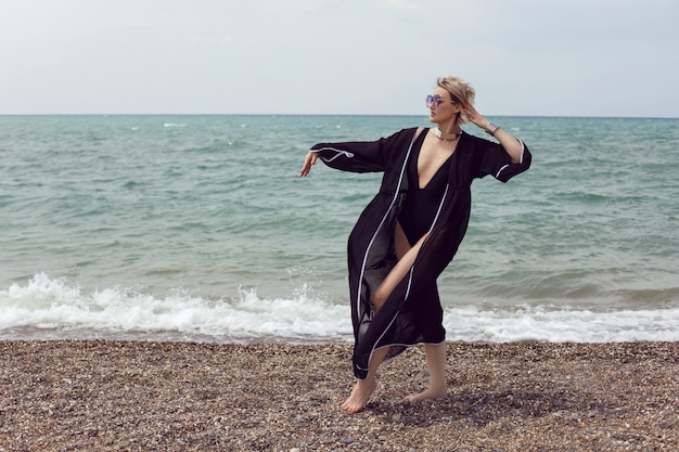 Sexy woman in a black swimsuit and sunglasses is stand on the beach in summer