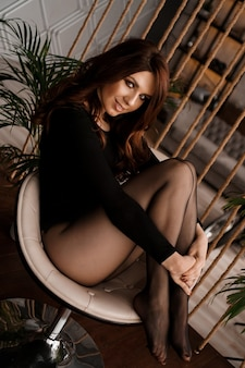 Sexy woman in black tights sitting on the chair