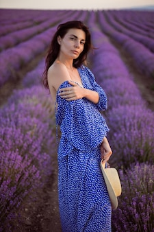 Sexy woman in a blue dress and a straw hat looks at the camera in blooming lavender fields at sunset enjoys nature