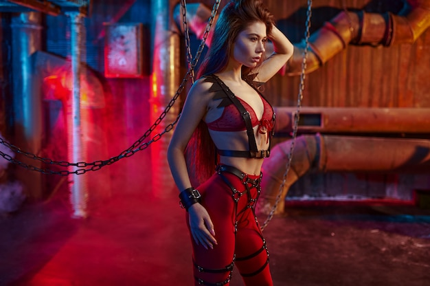 Sexy woman body in red bdsm suit chained up, abandoned factory interior. young girl in erotic underwear, sex fetish, sexual fantasy