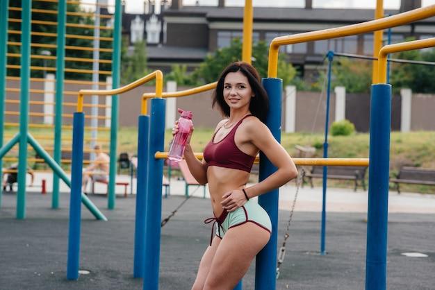 セクシーな女性はスポーツをし、屋外で水を飲みます。フィットネス。健康的な生活様式。