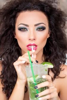 Sexy woman drinking mojito