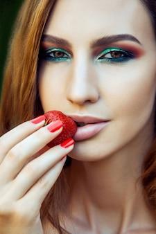 딸기를 먹는 섹시 한 여자. 관능적인 레드립스. 빨간 매니큐어와 천연 립스틱. 욕구. 딸기와 함께하는 섹시한 감성.
