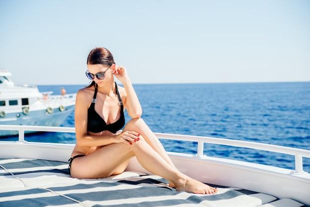 Sexy woman enjoying beach relaxing joyful in summer by tropical blue water. beautiful bikini model happy on travel