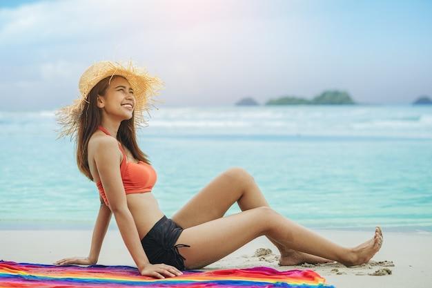 セクシーな女性の自由な休暇はビーチでリラックスして暖かい光でお楽しみください