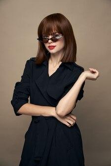 섹시 한 여자 안경 메이크업 빨간 입술 검은 코트 고립 된 배경