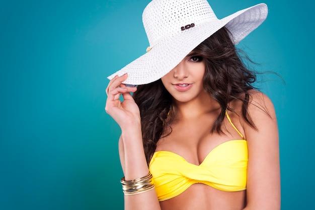 Donna sexy che si nasconde dietro il cappello bianco