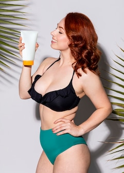 日焼け止めチューブを保持しているビキニのセクシーな女性