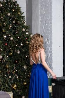 長い青いドレスのセクシーな女性は、クリスマスツリーのライトの上のお祝いリビングルームに立っています。新年とクリスマスのテーマ。お祝いの美しい長いブロンドの髪と休日mood.fashion女の子モデル