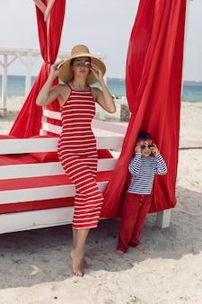 Сексуальная женщина в красном полосатом платье и соломенной шляпе стоит с маленьким мальчиком возле крытого шезлонга на пляже летом