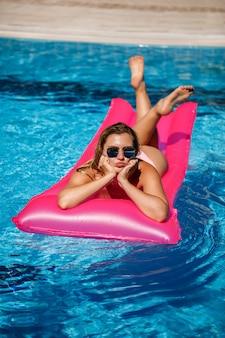 水着姿のセクシーな女性は、プールのピンクのインフレータブルマットレスの上に横たわっています。暑い夏の晴れた日には、プールサイドでおくつろぎください。休暇の概念