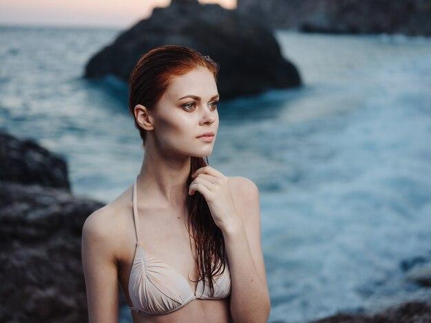 Сексуальная женщина в купальнике на пляже у моря в природе жесты руками.