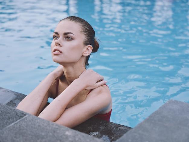 水着姿のセクシーな女性がプールで泳ぎ、ひじでタイルに寄りかかる