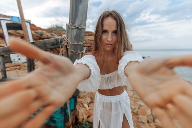 岩の多い海岸の難破船で白いドレスを着たセクシーな女性