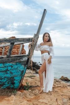 Сексуальная женщина в белом платье у потерпевшего крушение корабля на скалистом берегу моря