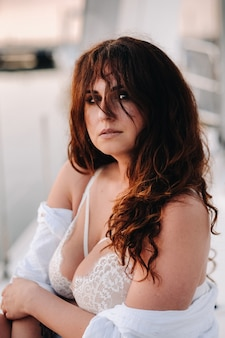 Сексуальная женщина в белой рубашке наслаждается закатом на своей частной белой яхте.