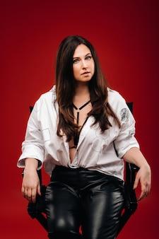Сексуальная женщина в белой рубашке сидит на черном стуле на красном фоне