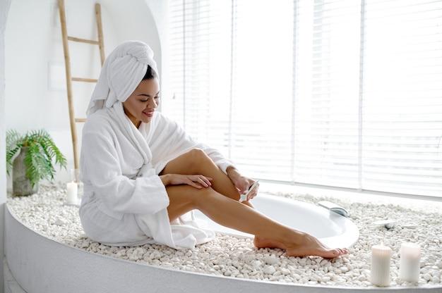 浴槽の端に座っているバスローブを着たセクシーな女性。バスタブの女性、スパの美容とヘルスケア、バスルームのウェルネストリートメント、背景の小石とキャンドル