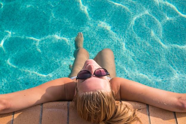 여름 햇살을 즐기고 수영장에서 휴가 기간 동안 선탠하는 비키니에있는 섹시 한 여자. 평면도. 수영장에서 여자입니다. 비키니 입은 섹시한 여자.