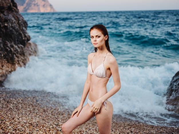 비키니 모델 수영복 젖은 머리 투명 바다 물 흰색 거품에 섹시 한 여자.