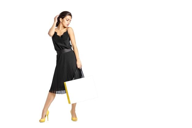 흰색 배경에 고립 된 쇼핑백과 검은 드레스에 섹시 한 여자.