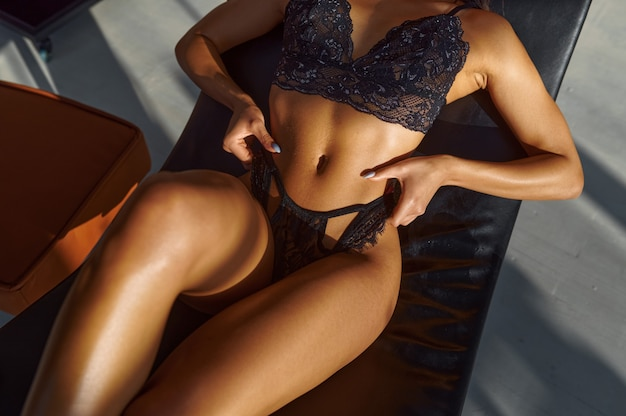 가죽 sunbed에서 포즈 검은 란제리에 섹시 한 여자