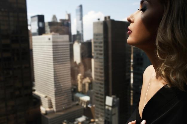 Сексуальная женщина в черном шелковом халате стоит с обнаженными плечами перед панорамным окном в нью-йорке