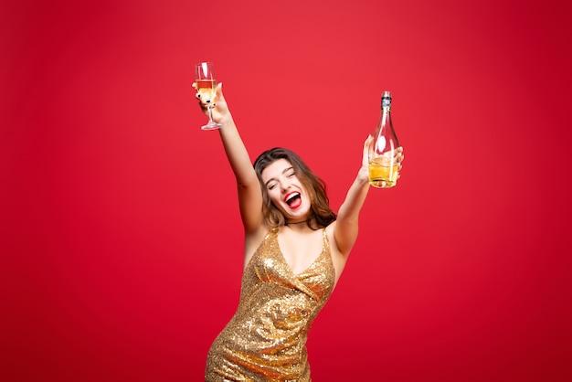 赤い口紅の飲み物シャンパンとゴールドのドレスでセクシーな女性