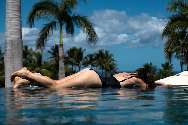 無限のエキゾチックなスイミングプールでセクシーな女性