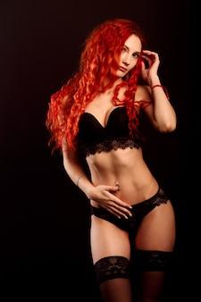 黒の背景、赤い髪のランジェリーでセクシーな女性