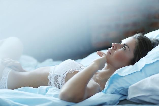 침대에 누워 란제리에 섹시 한 여자