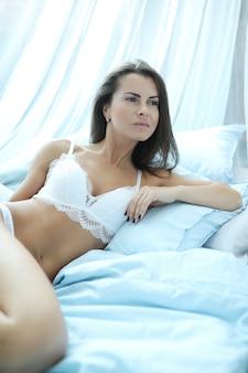 ベッドに横になっているランジェリーのセクシーな女性
