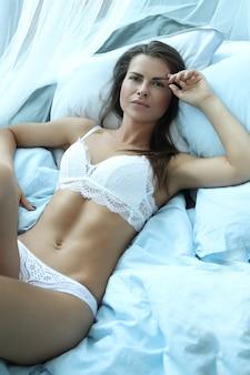Сексуальная женщина в нижнем белье, лежа на кровати